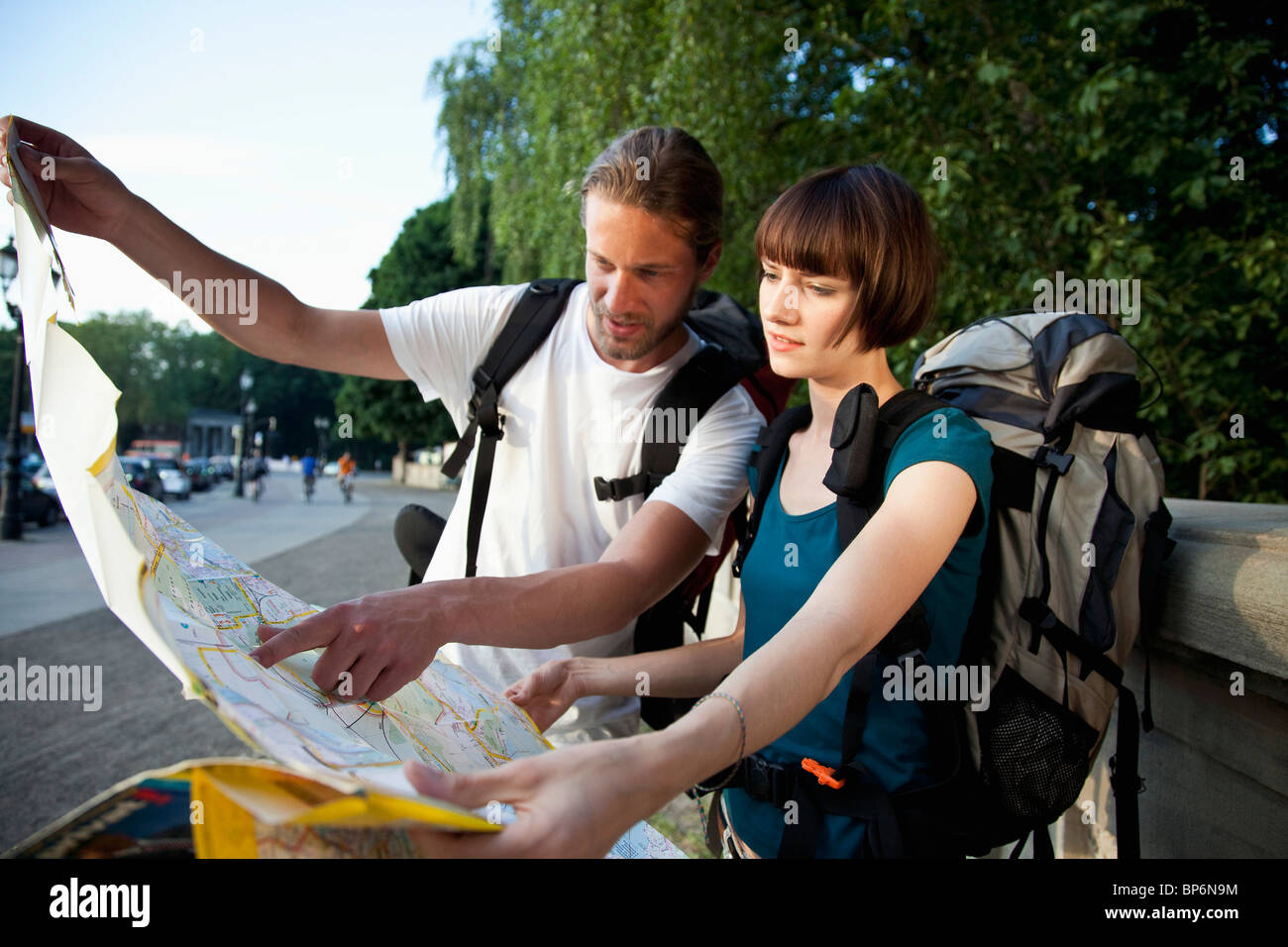 Un joven mochilero pareja mirando un mapa de la ciudad Foto de stock