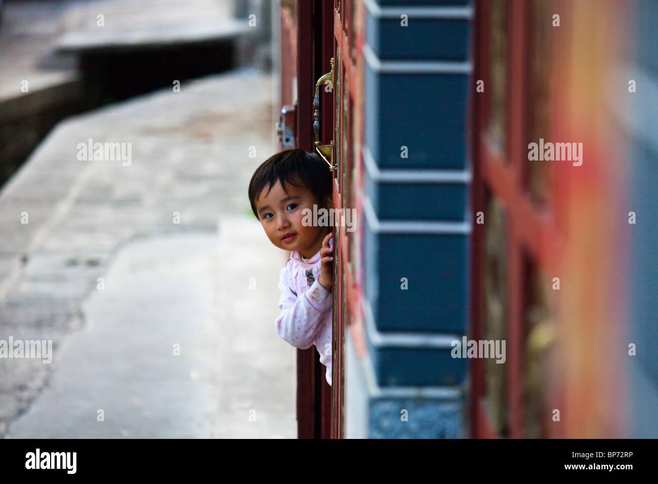 Joven china peeking alrededor de una esquina en Dali, provincia de Yunnan, China Imagen De Stock