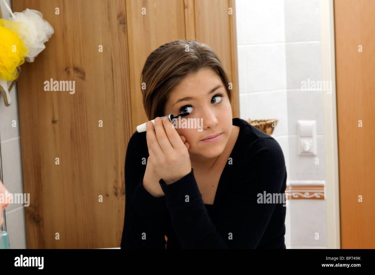 Chica de aplicar el rímel para los ojos delante de un espejo Imagen De Stock