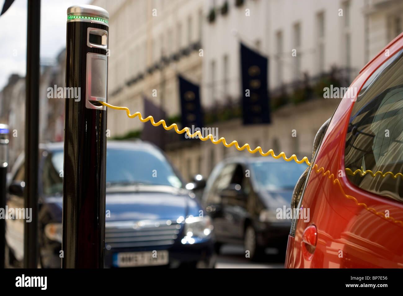 Coche eléctrico en una calle de Londres están cargando. Imagen De Stock