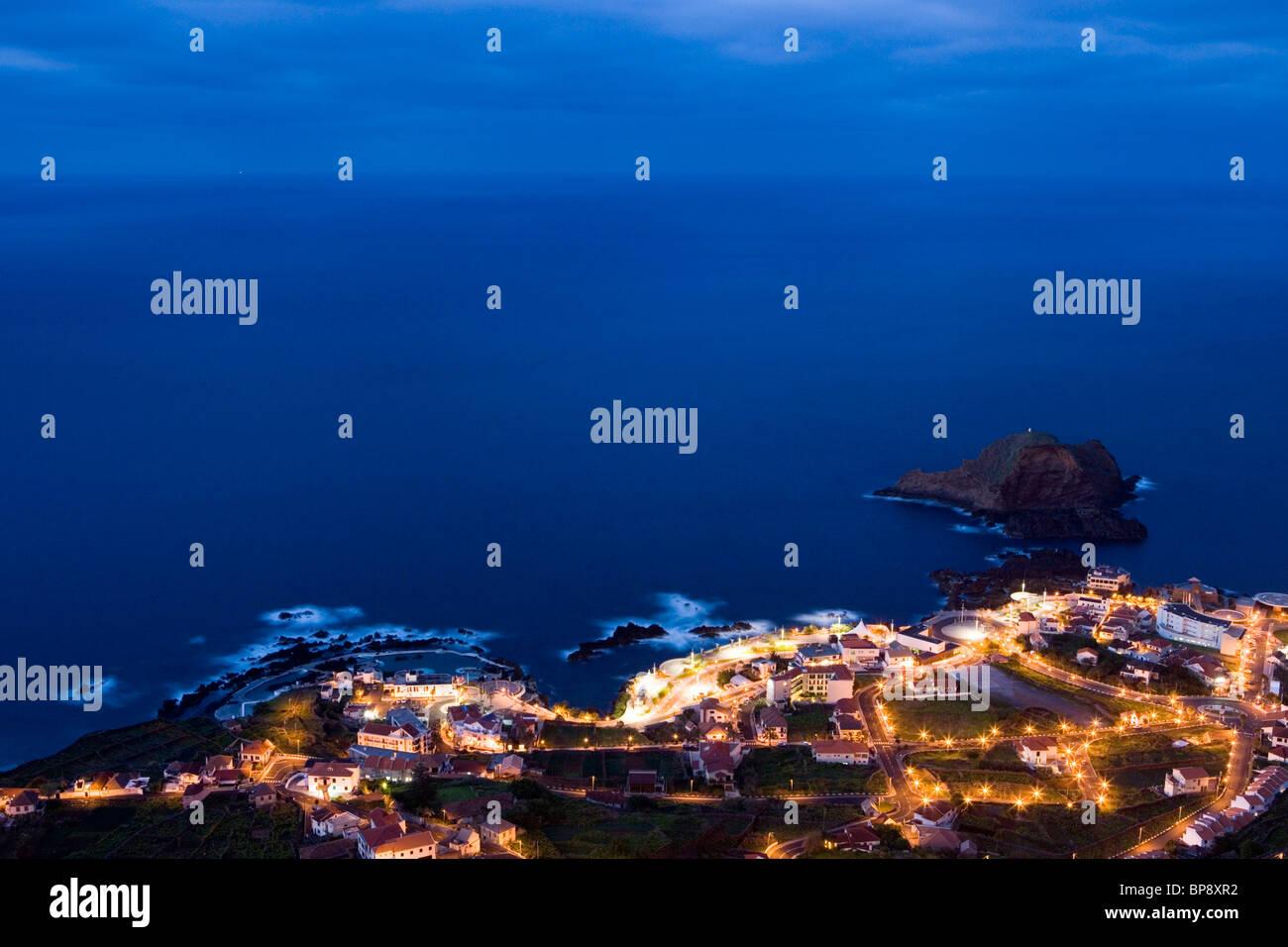 Ciudad y piscinas de roca natural, visto desde el Miradouro da Santinha mirador al atardecer, Porto Moniz, Madeira, Foto de stock