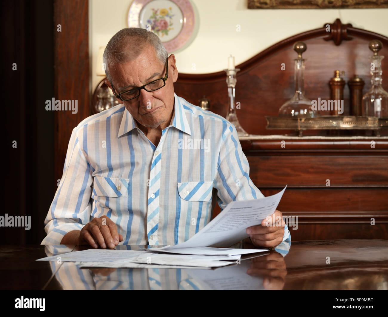 Anciano sentado en una mesa mirando a través de facturas con la infeliz expresión en su rostro. Imagen De Stock