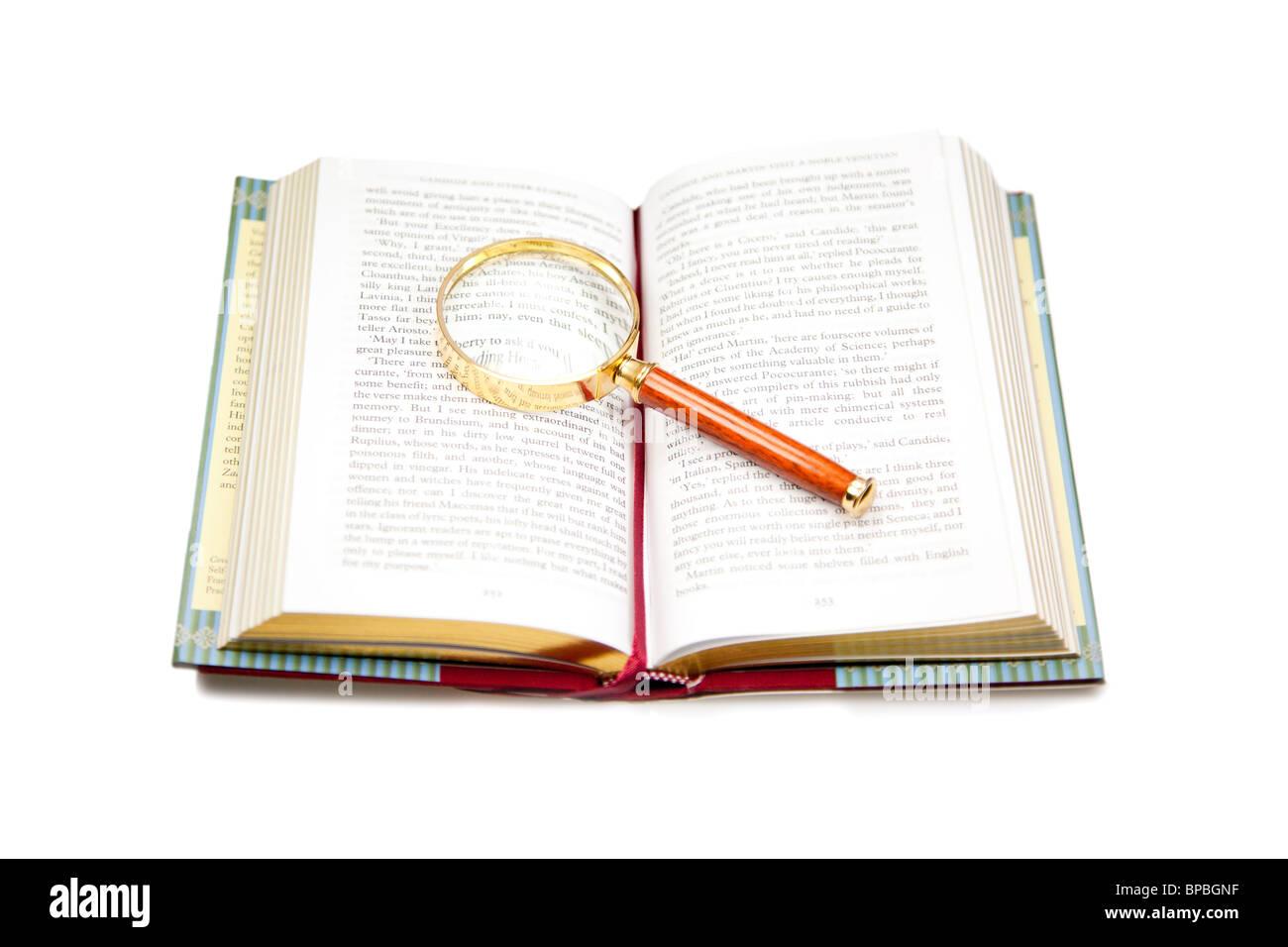 Libro Abierto con lupa aislado en blanco. Imagen De Stock