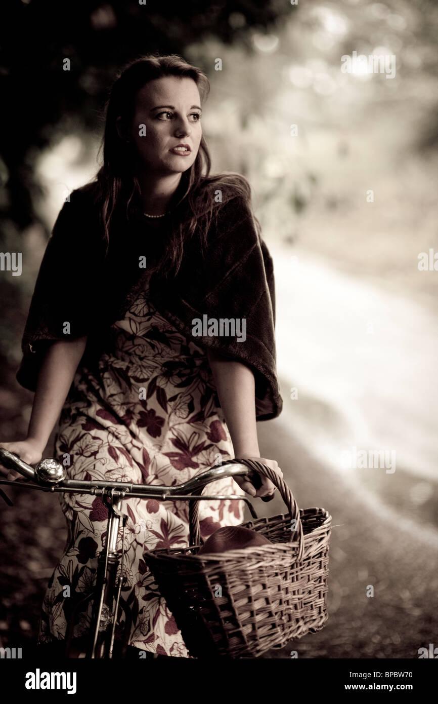 Chica con una bicicleta en un estilo vintage 1940 Imagen De Stock