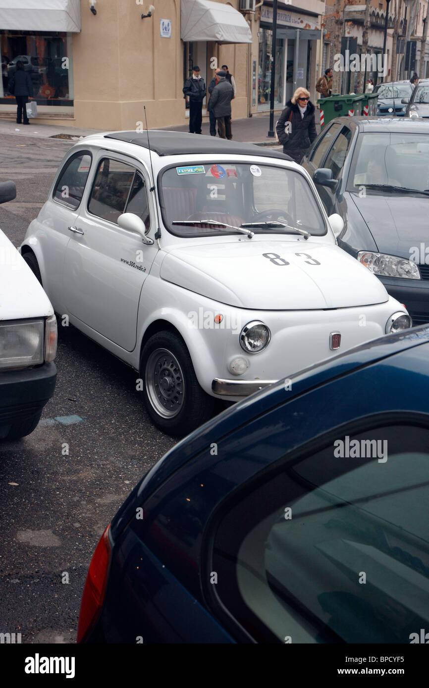 Un coche pequeño Fiat 500 estacionado en una segunda fila, Oristano, Italia Foto de stock