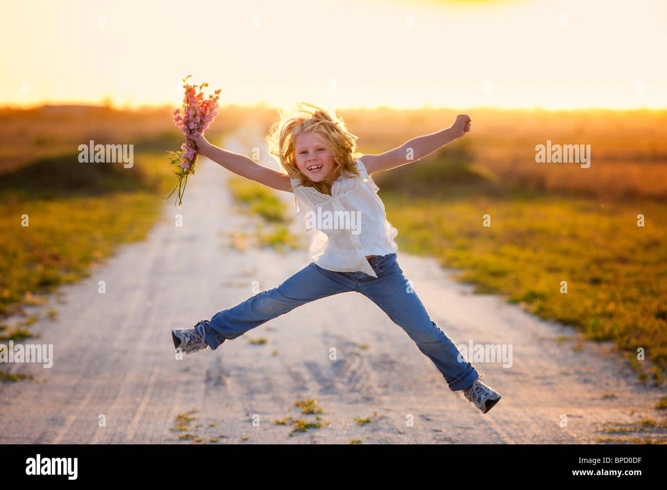 Joven sosteniendo flores saltar en el aire Imagen De Stock