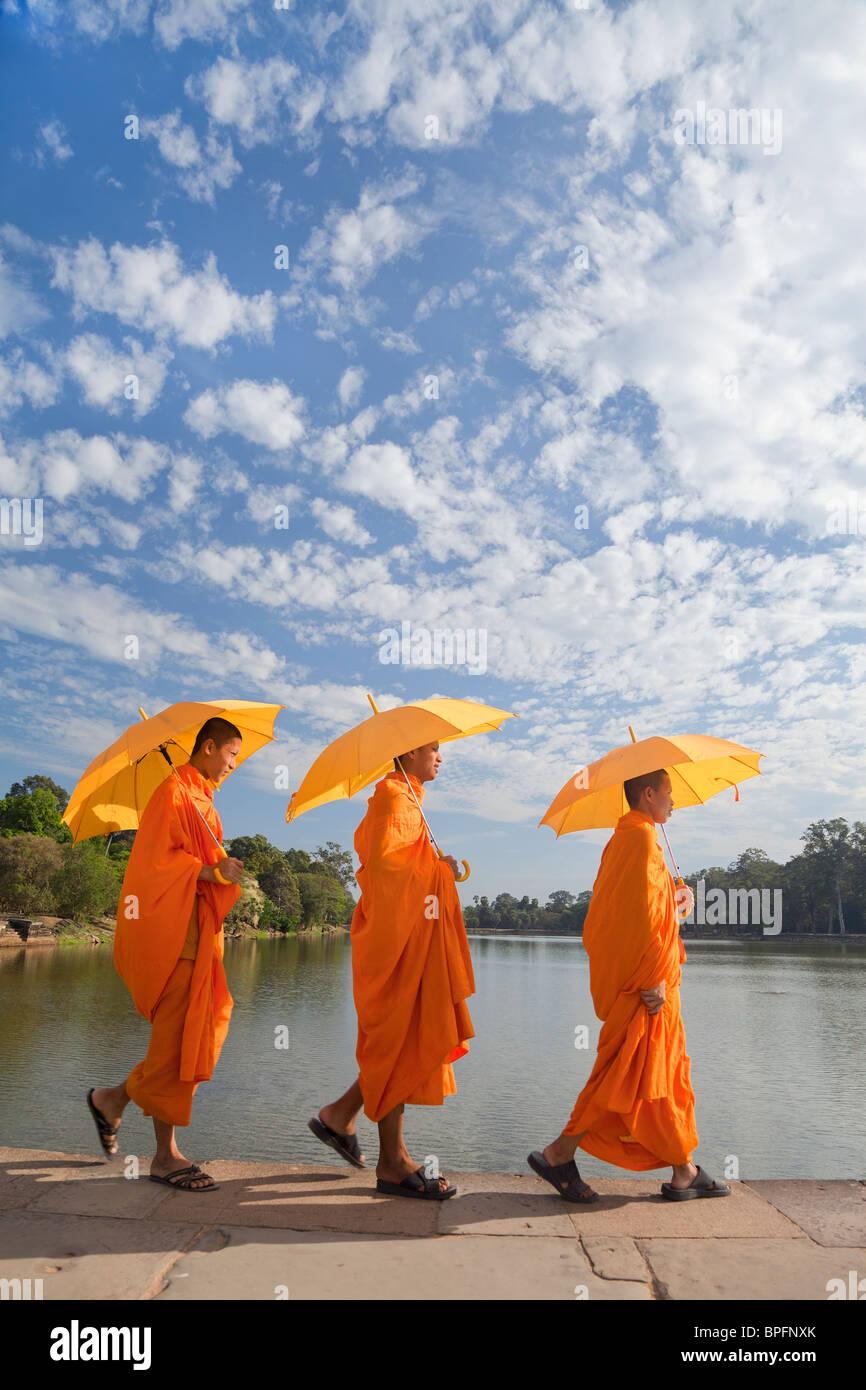 Tres Monjes por el foso que rodea el complejo de templos de Angkor Wat, Siem Reap, Camboya, Sudeste de Asia Imagen De Stock