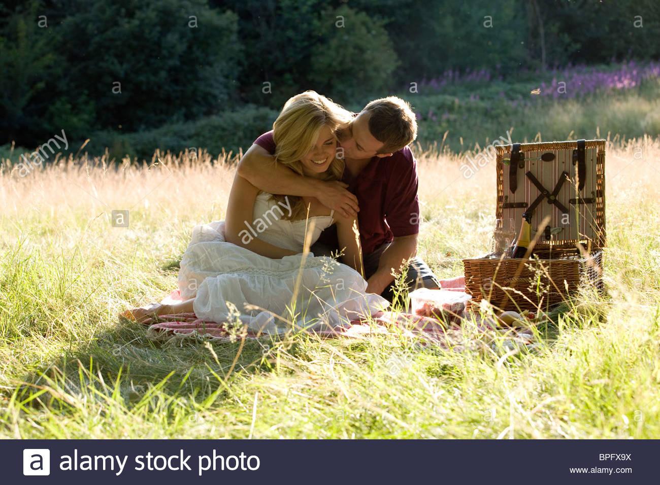 Una joven pareja haciendo un picnic, abrazando Imagen De Stock