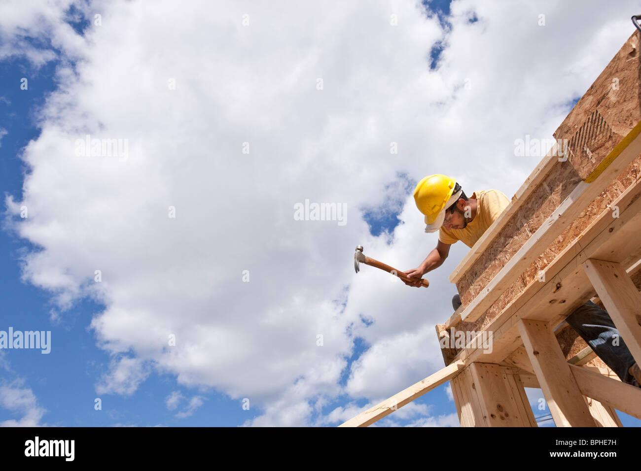 Carpintero martillando las viguetas del piso superior Imagen De Stock
