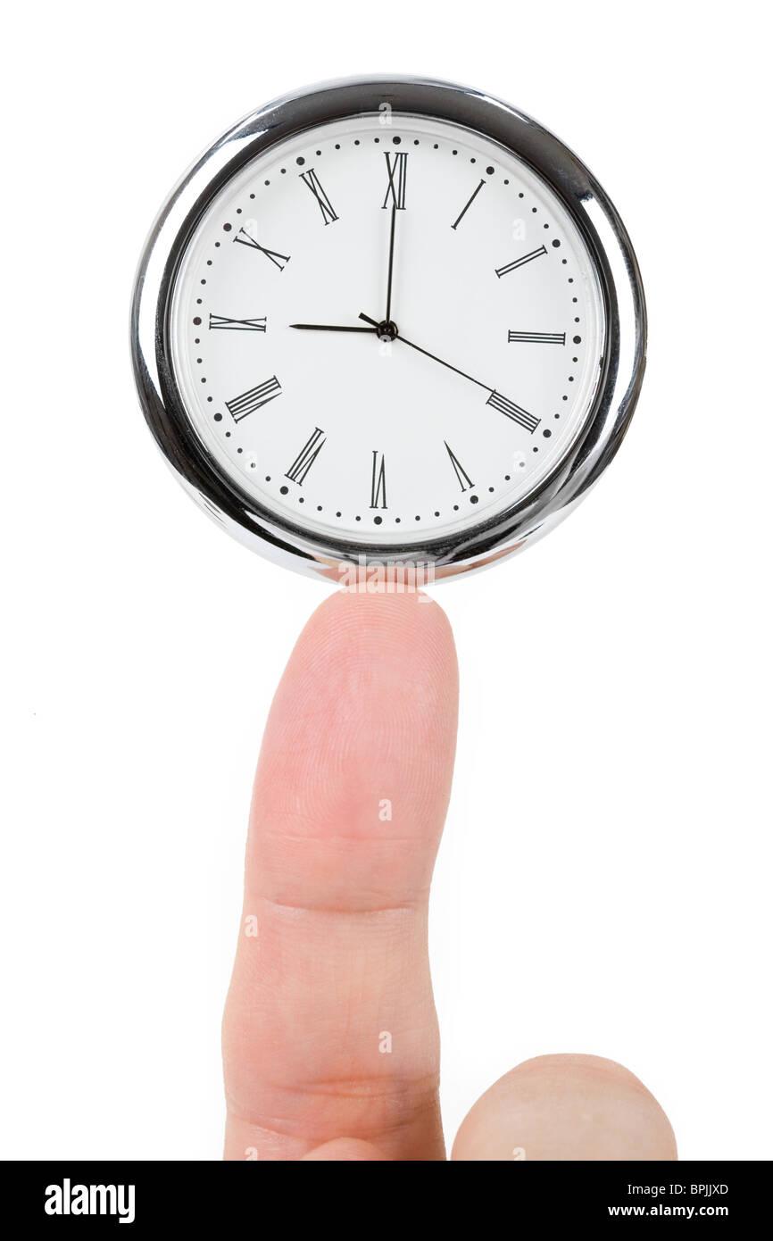 Reloj y dedo, concepto de saldo de tiempo Imagen De Stock