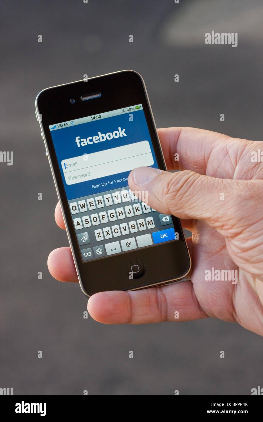 El iPhone 4 en la palma de la mano de un hombre. En la pantalla se puede ver la aplicación de Facebook. Imagen De Stock