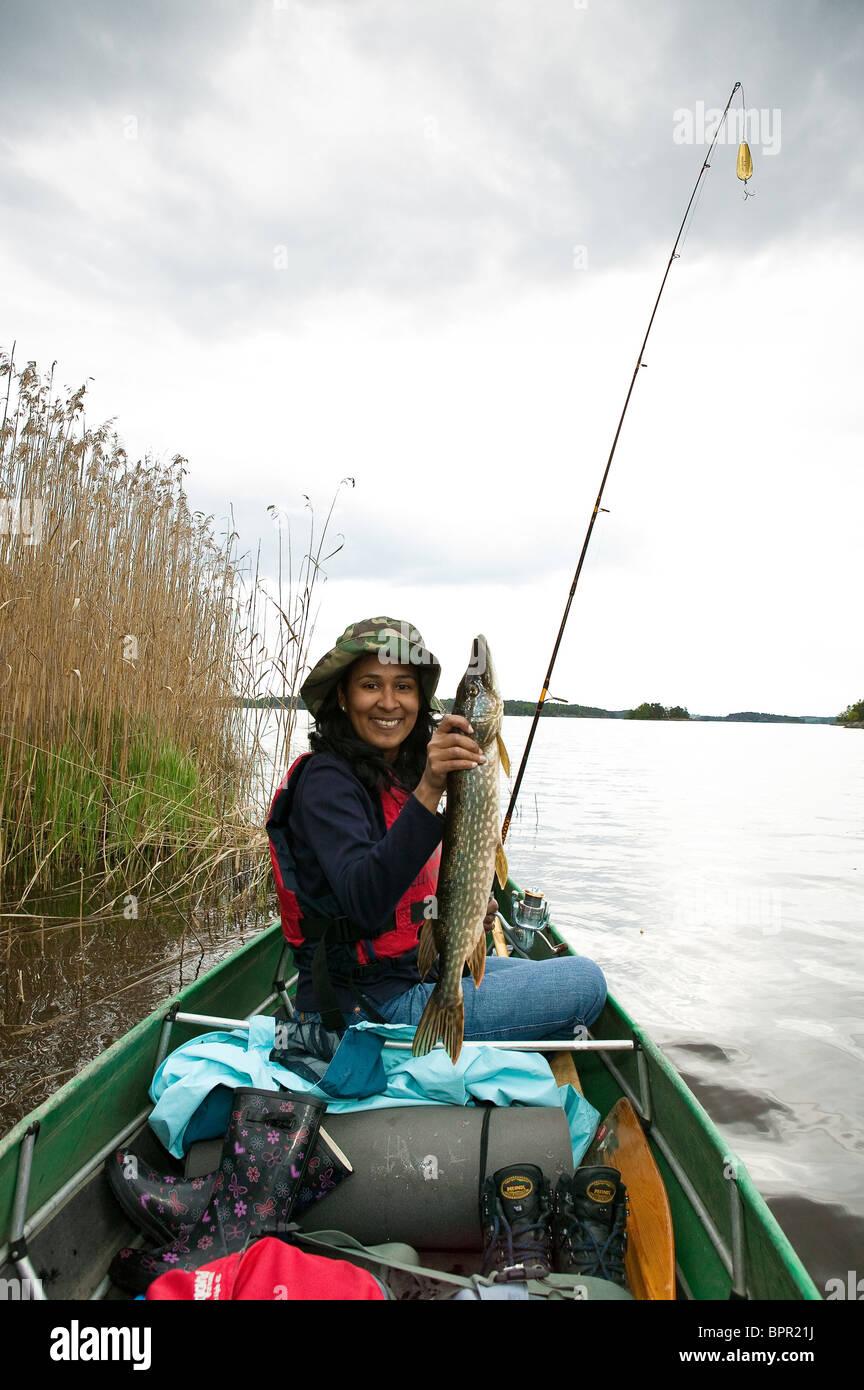 Chica con un norte de Pike, Esox lucius, capturados en el lago Vansjø, Østfold fylke, Noruega. Imagen De Stock