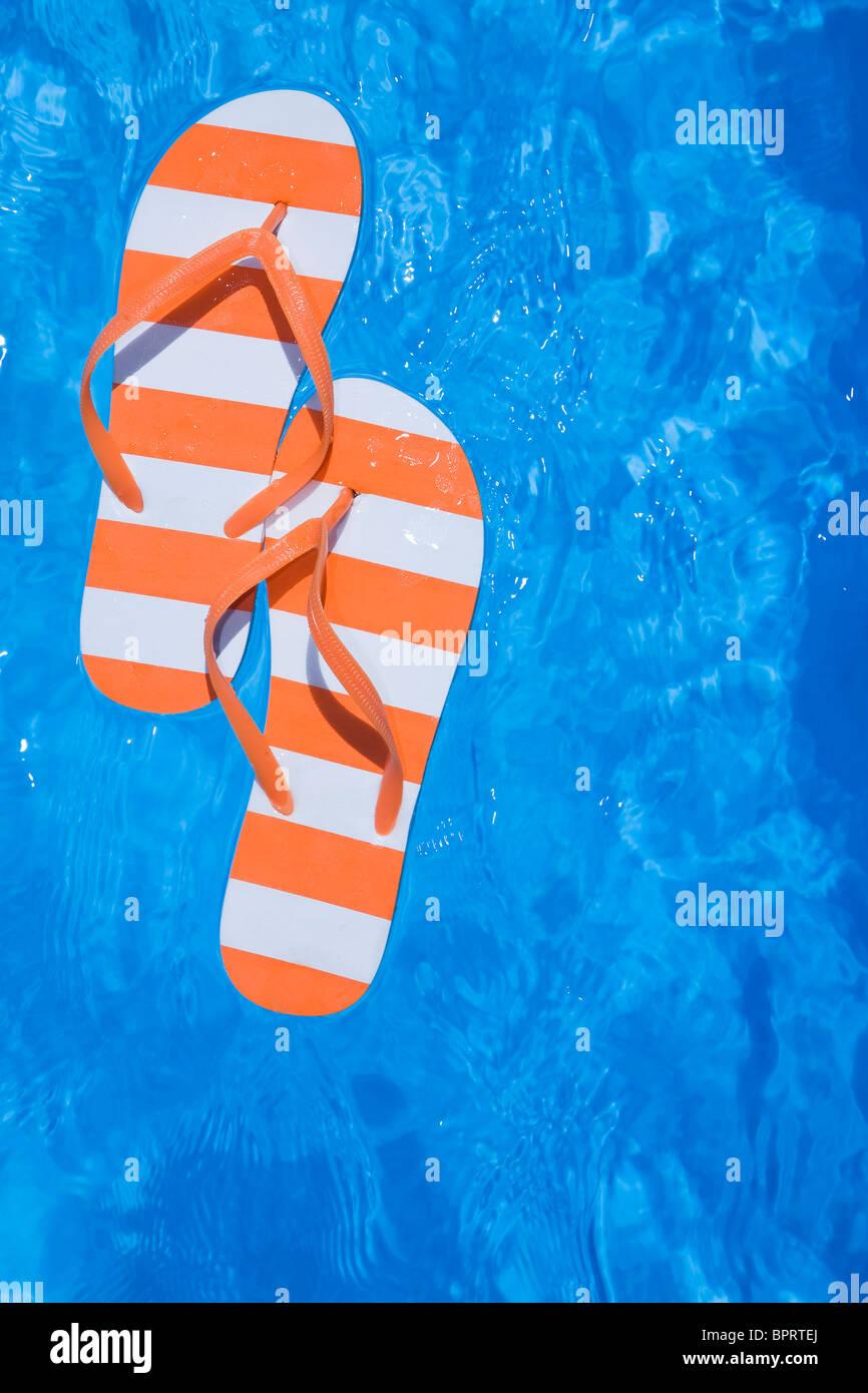 Stripey bastante par de sandalias o chanclas en una piscina azul brillante Imagen De Stock