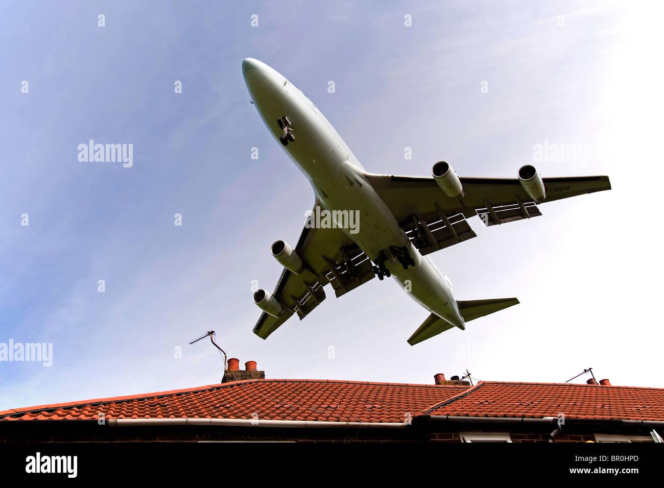 Boeing 747 Jumbo jet aterrizando sobre los tejados de la casa al final de la pista de aterrizaje en el aeropuerto Imagen De Stock