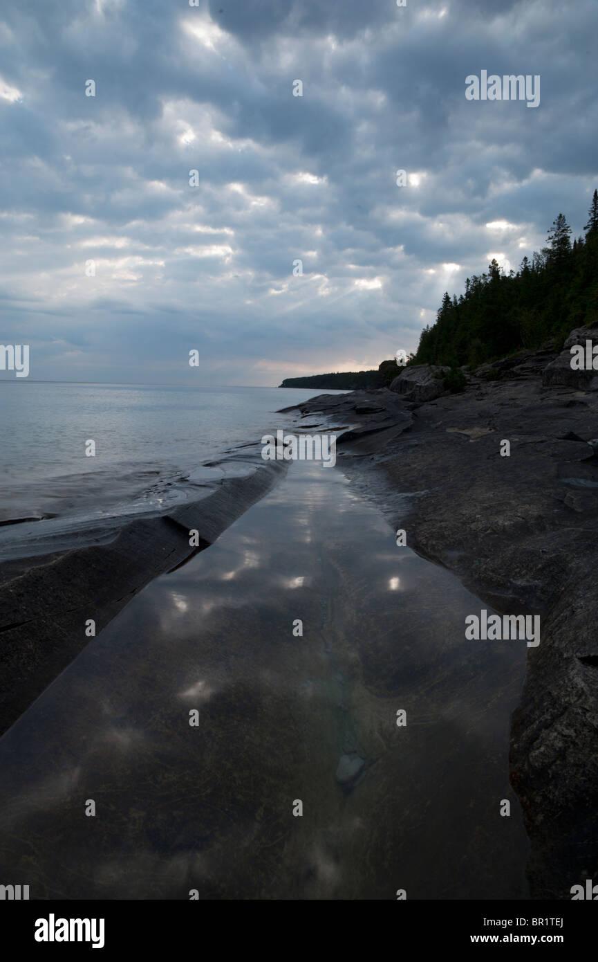 La orilla de la calita reflejando nubes justo después del amanecer en la península de Bruce Foto de stock
