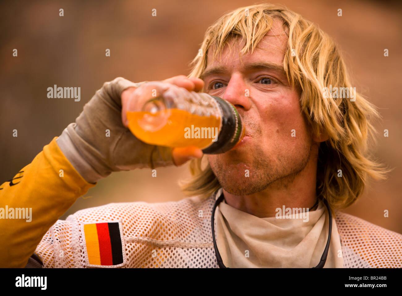 Hombre bebiendo una bebida energética durante una carrera de aventura cerca de Moab, Utah. Imagen De Stock