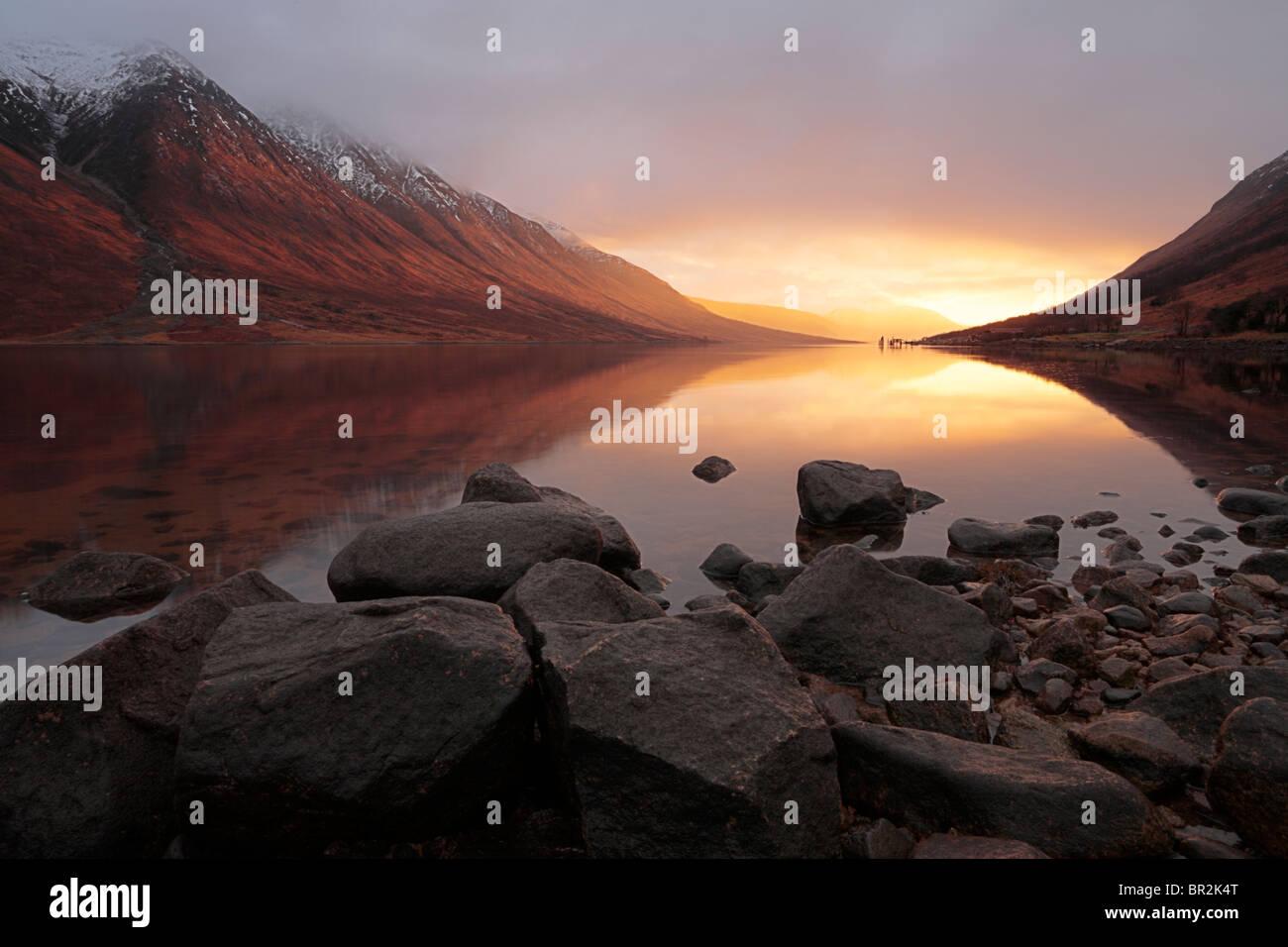 Luz llameante de una puesta de sol de invierno ilumina Loch Etive en las Tierras Altas de Escocia. Foto de stock