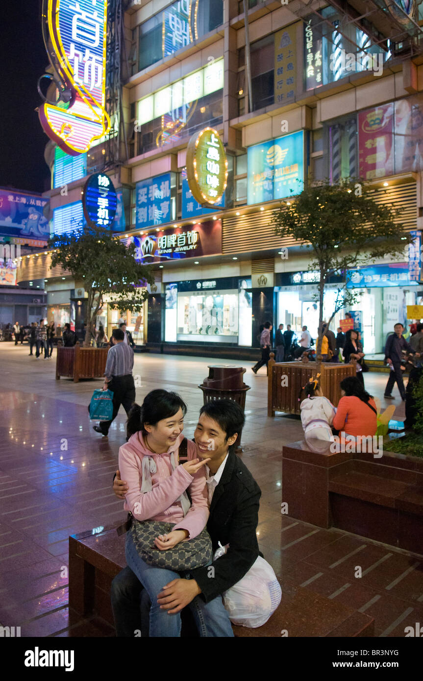 Pareja joven acurrucamos en calle peatonal, la Calle Nanjing, Shanghai, China Imagen De Stock