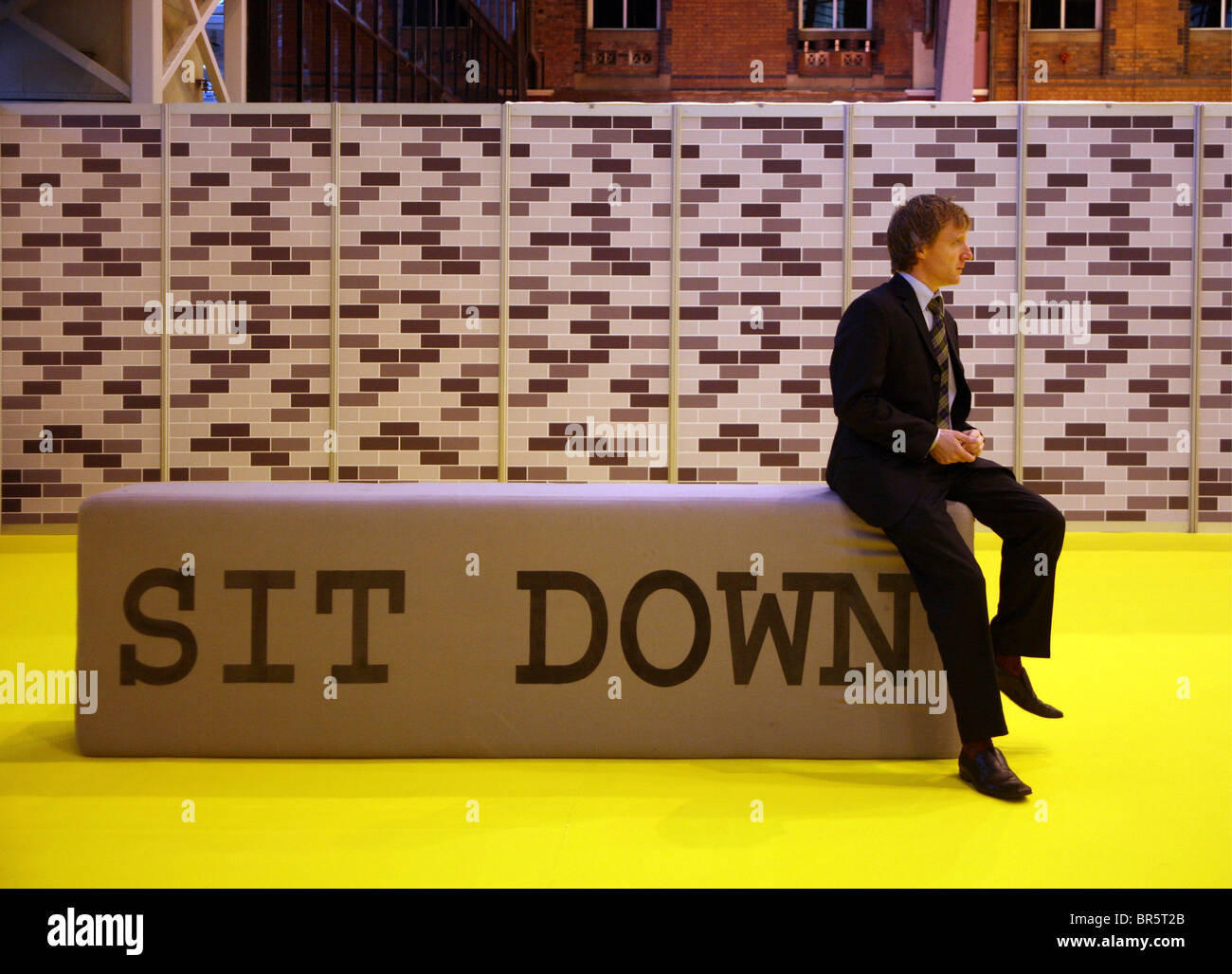 Un hombre se sienta en un 'abajo' cartel ubicado en la entrada de una conferencia de negocios. Imagen De Stock