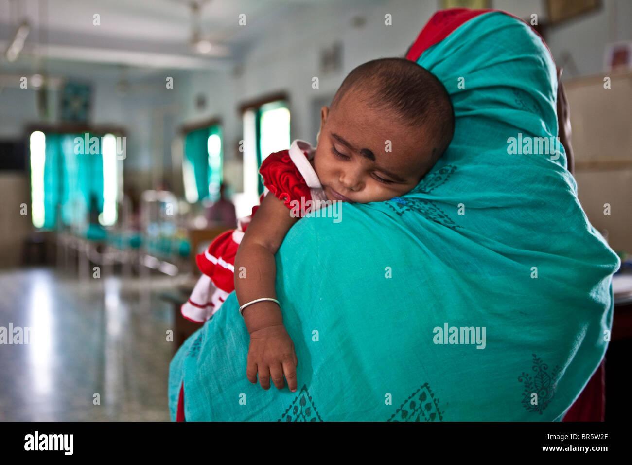 Una madre lleva a su bebé al niño necesitado Instituto urgencias. Led de ONGS de salud. Imagen De Stock