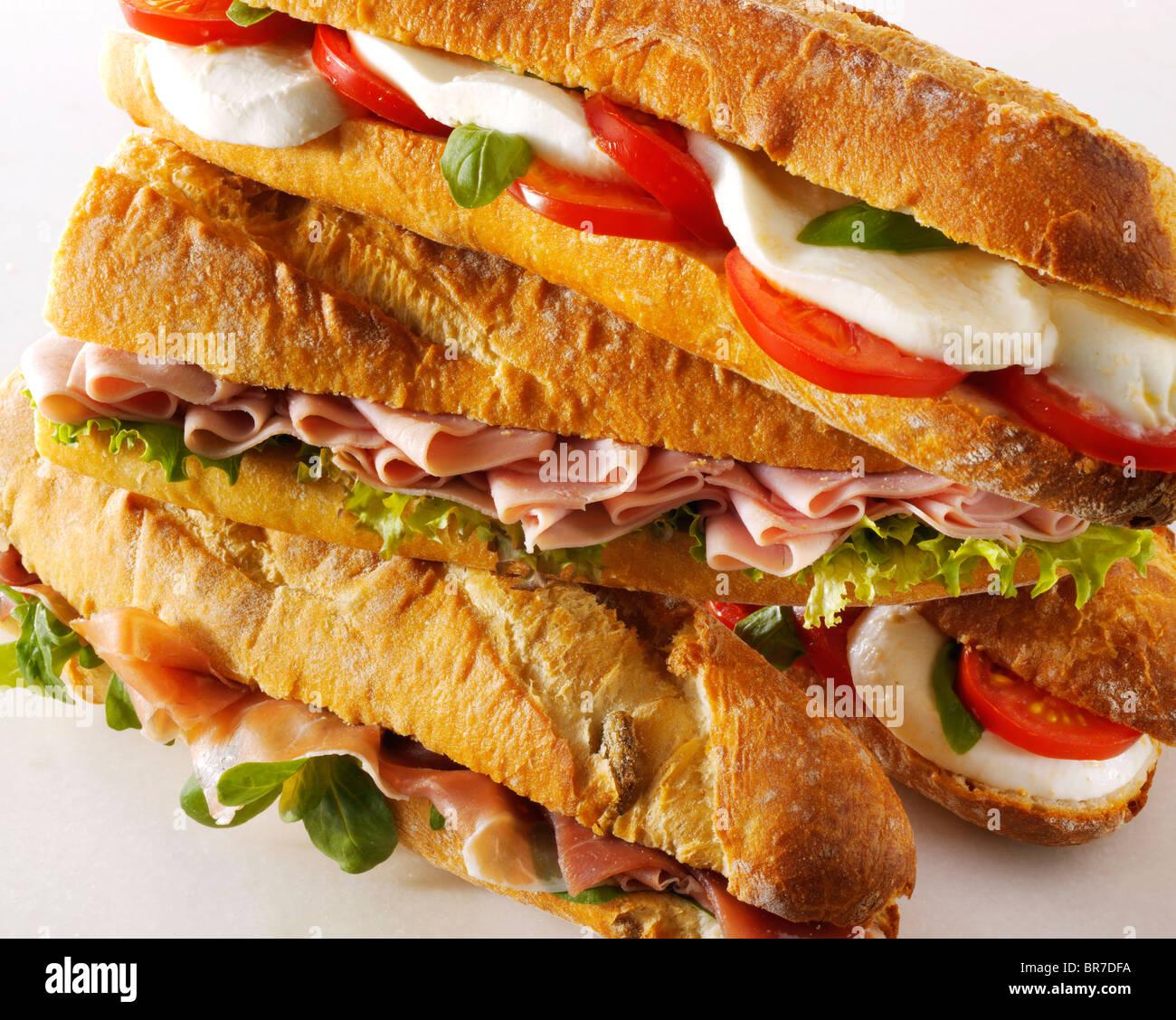 Pan baguette rellena con mozerella & tomates, jamón, ensalada, jamón Prcutto & Rocket. Imagen De Stock