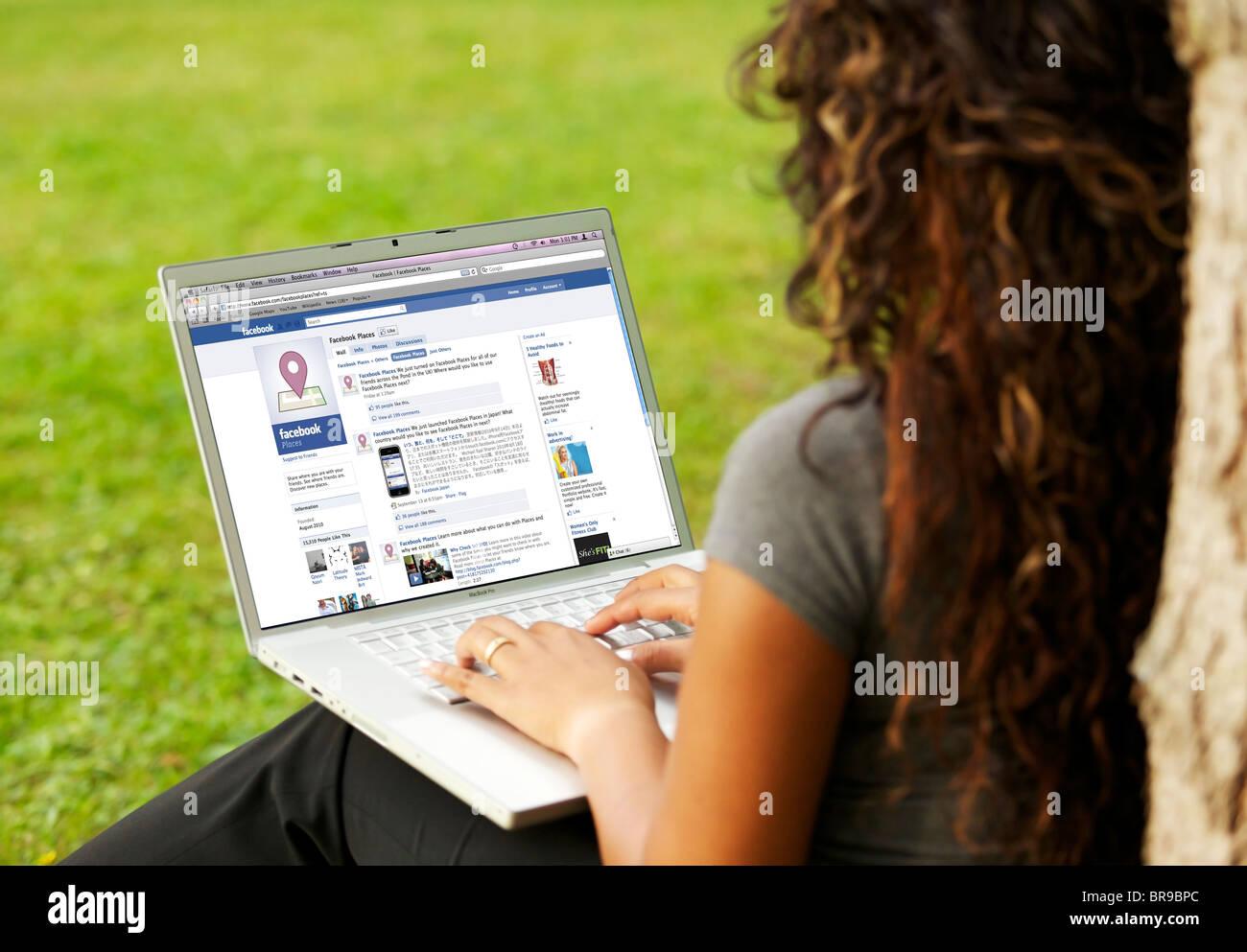 Mujer joven leer el nuevo 'Facebook Places' característica de la página en línea en un solo Imagen De Stock