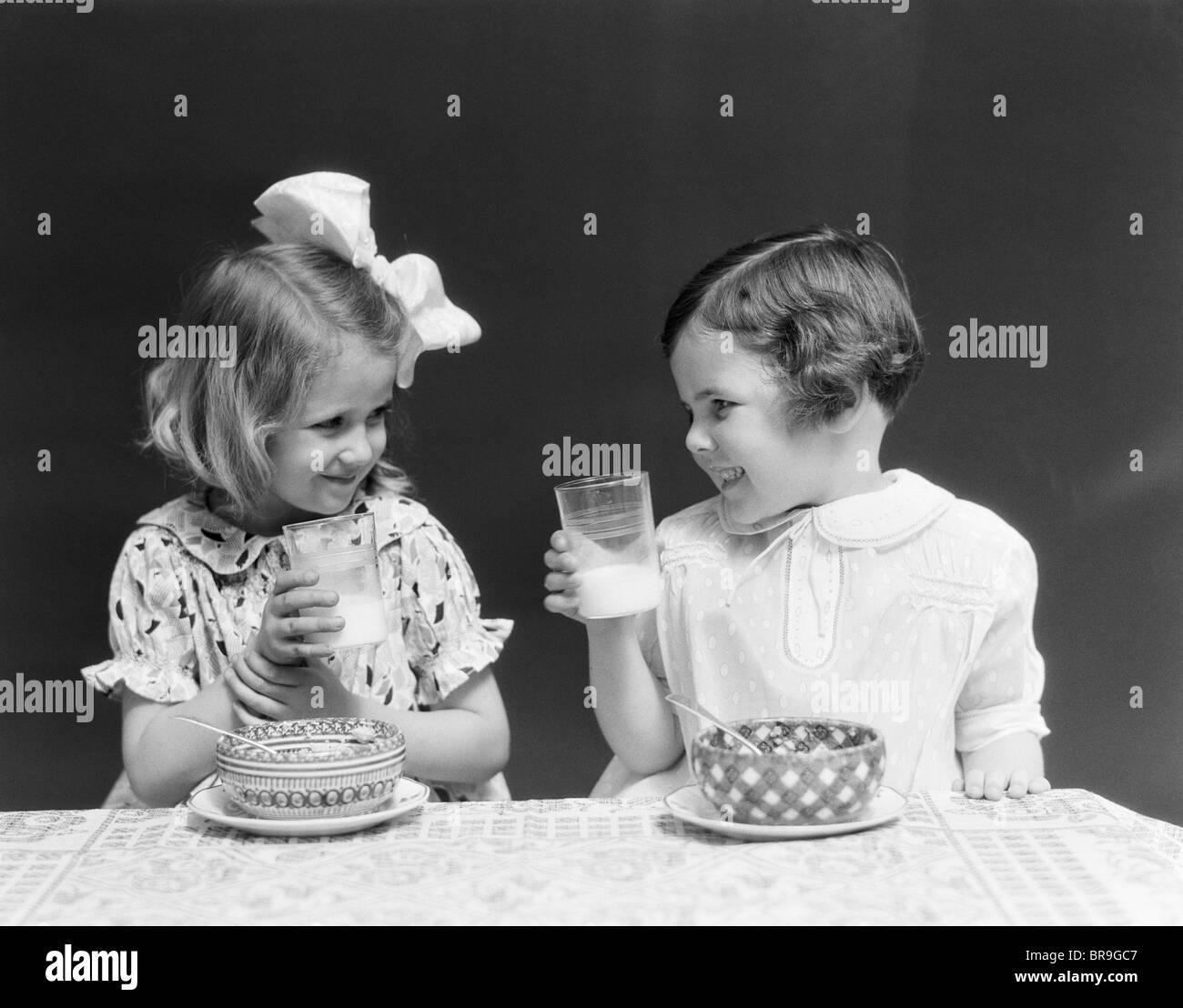 1930 dos niñas sonrientes beber leche tazón de cereales hablando riendo comer Imagen De Stock