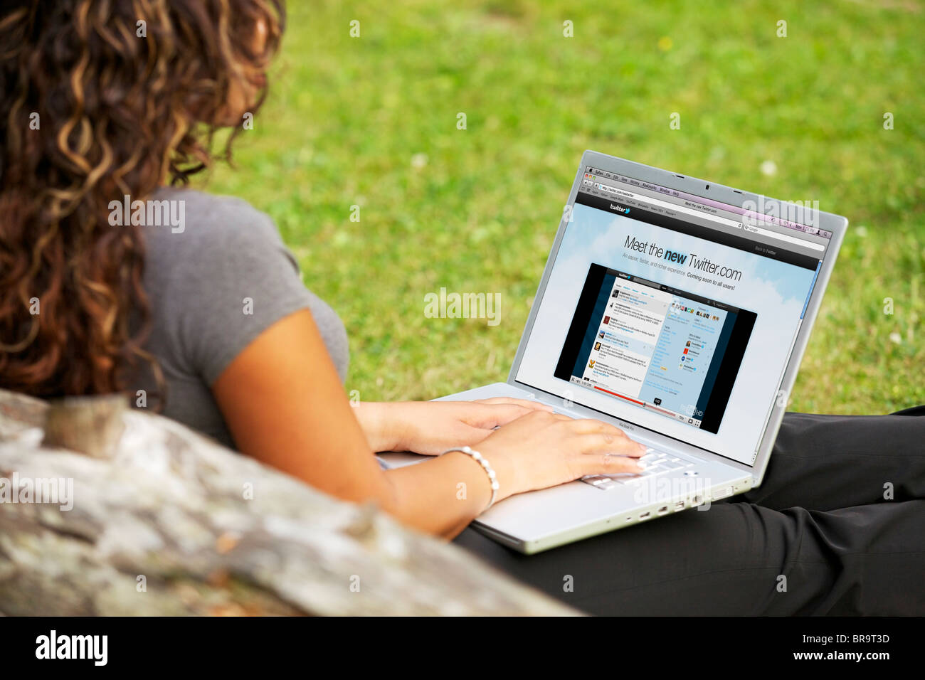 Mujer joven control de la nueva página de Twitter online en un portátil a solas en el parque Imagen De Stock