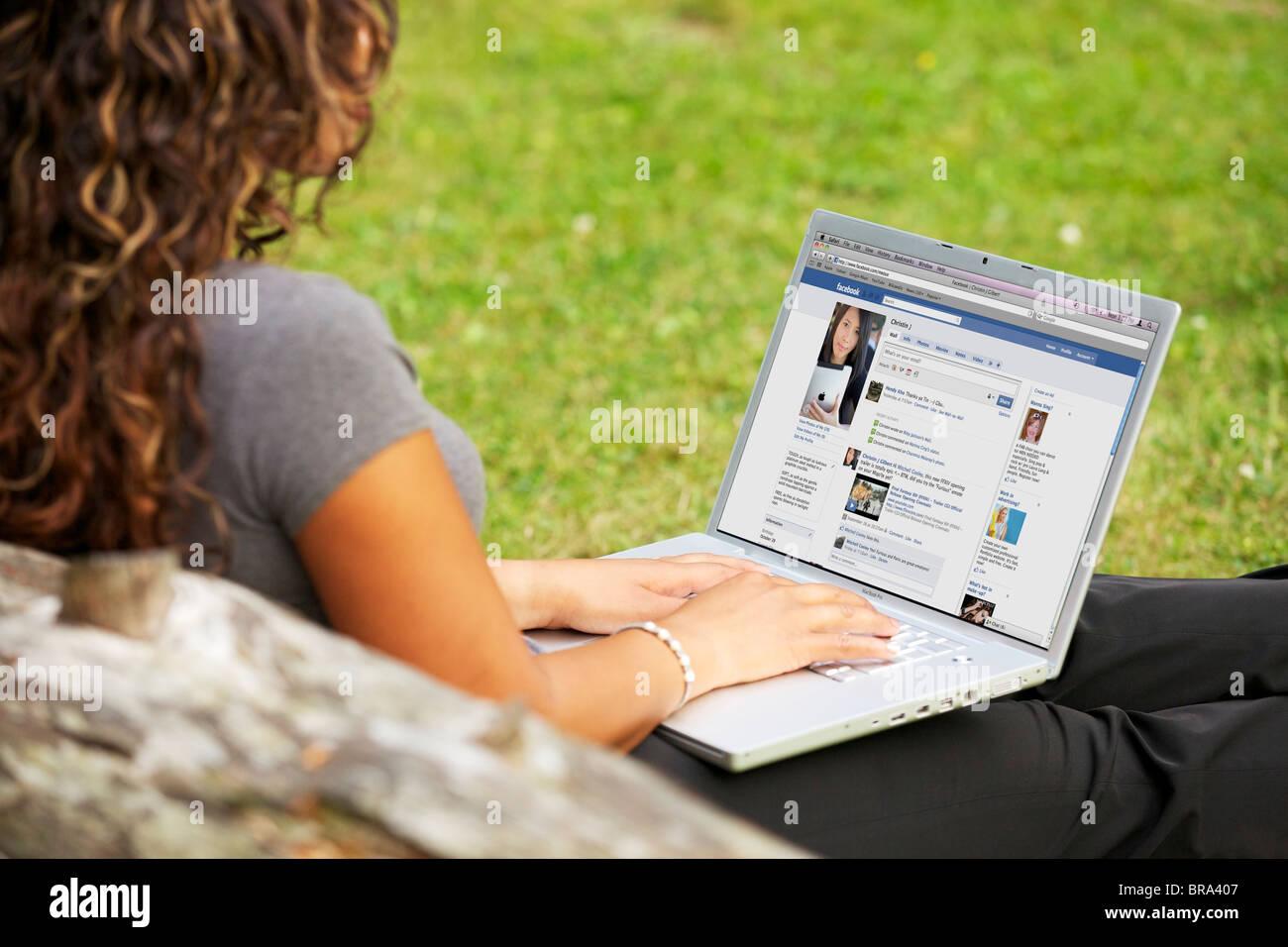 Mujer joven comprobación en línea de la página de Facebook en una laptop a solas en el parque Imagen De Stock