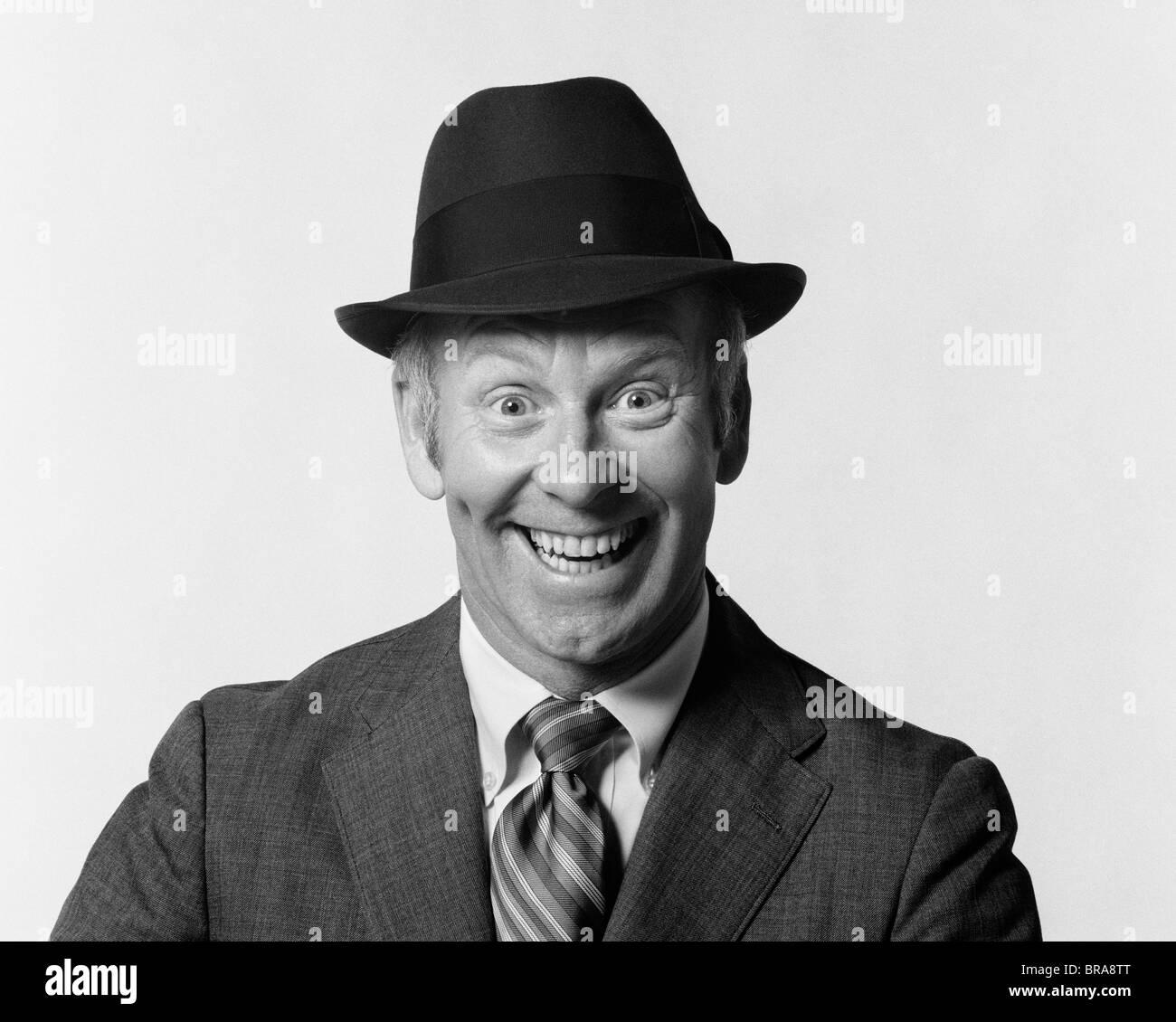 1960 Hombre sonriente vestidos de traje y sombrero con tonto ansiosos la expresión facial Foto de stock