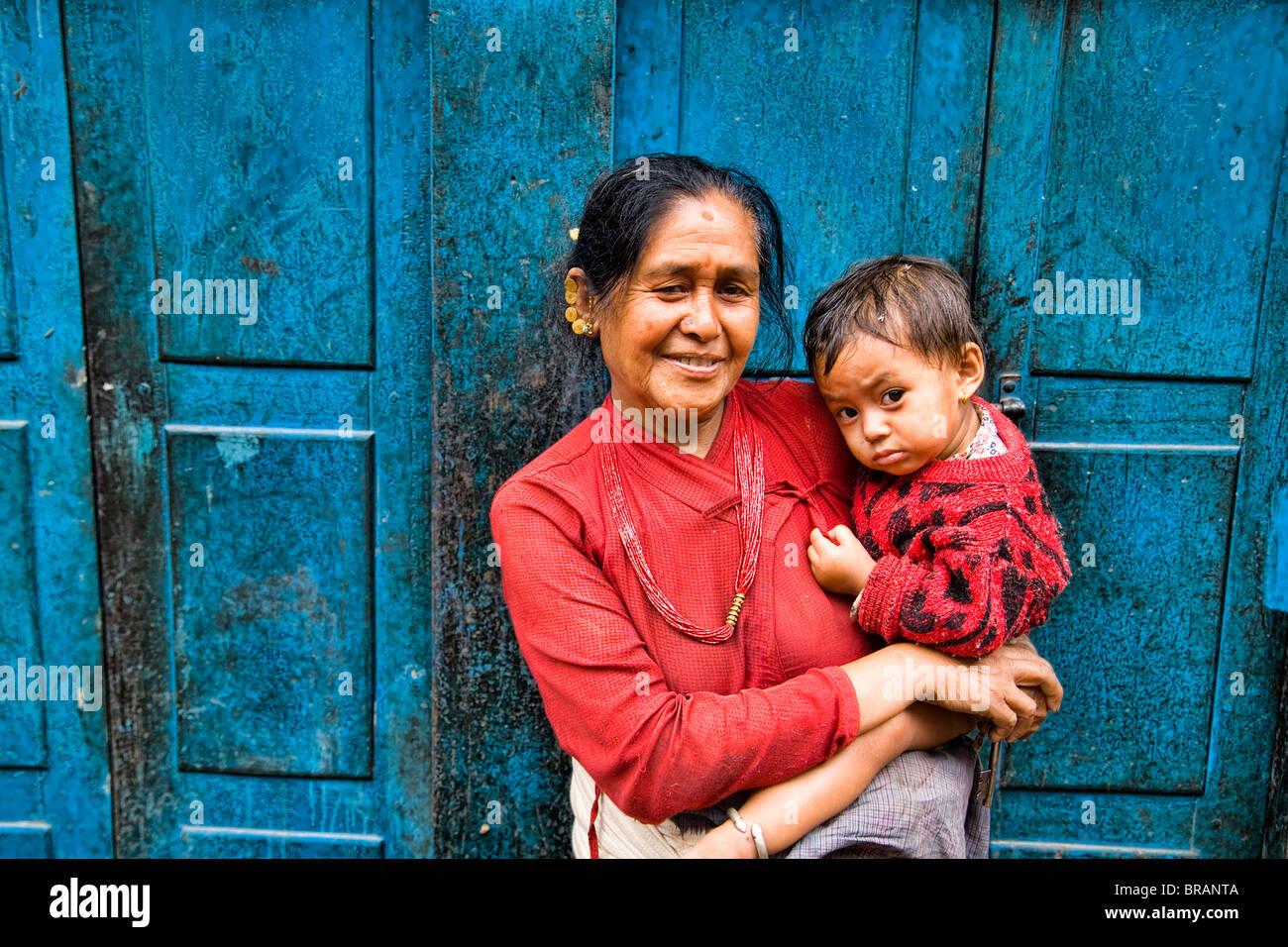 Mujer local con gran hijo en brazos en la aldea en una ciudad de Bhaktapur, cerca de Katmandú Nepal Foto de stock