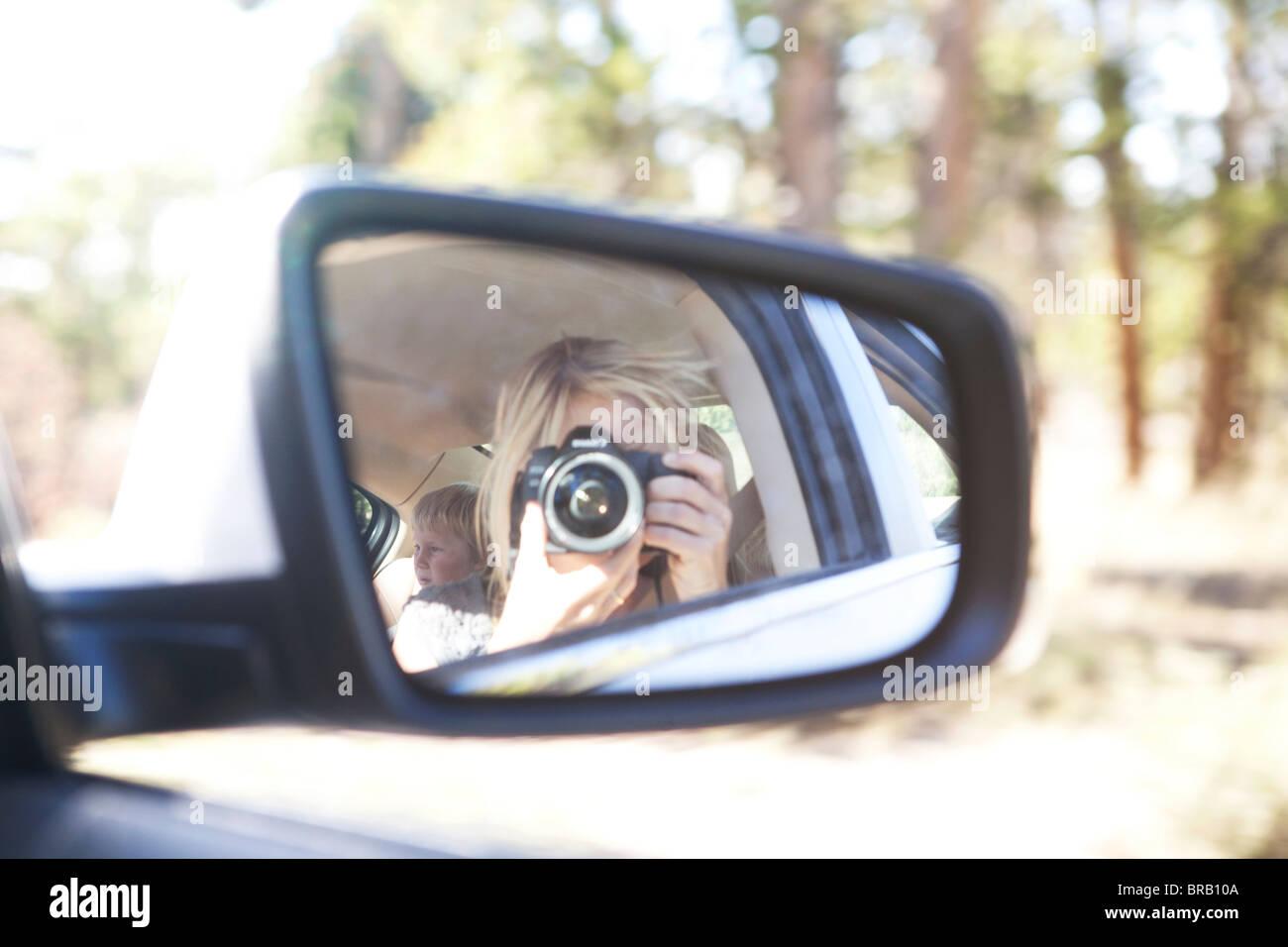 Mujer tomando fotos en el espejo lateral del coche Imagen De Stock