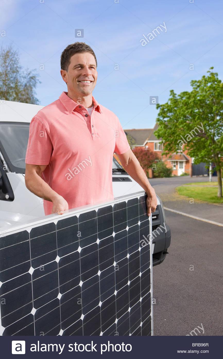 El hombre lleva cruzando la calle con panel solar Imagen De Stock