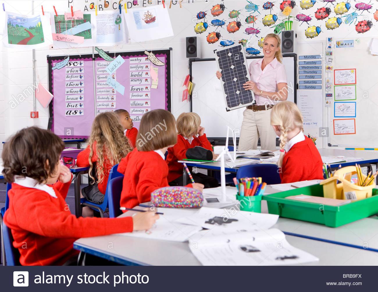 Profesor explicando los paneles solares a la escuela niños en el aula Imagen De Stock