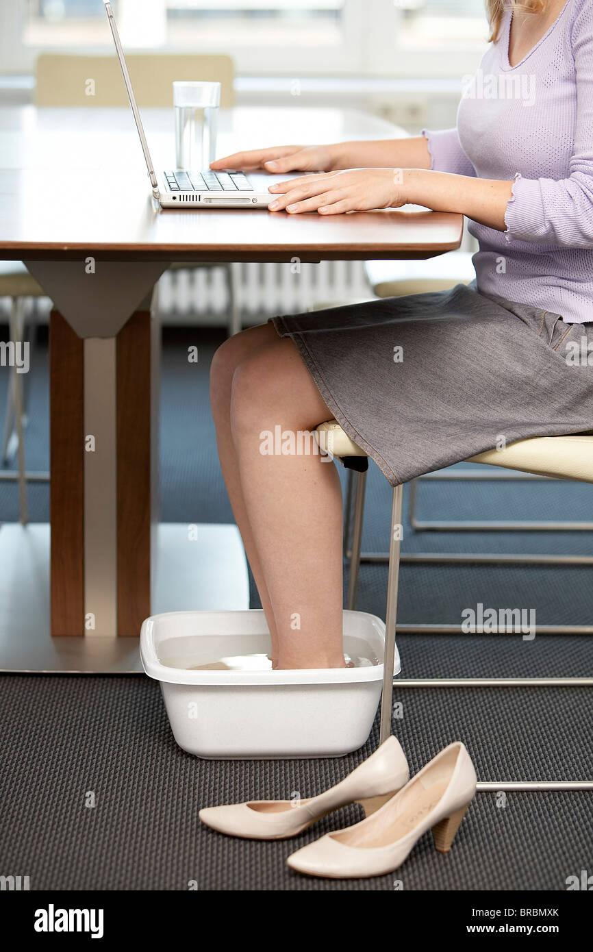 Mujer toma pediluvio en la oficina Imagen De Stock
