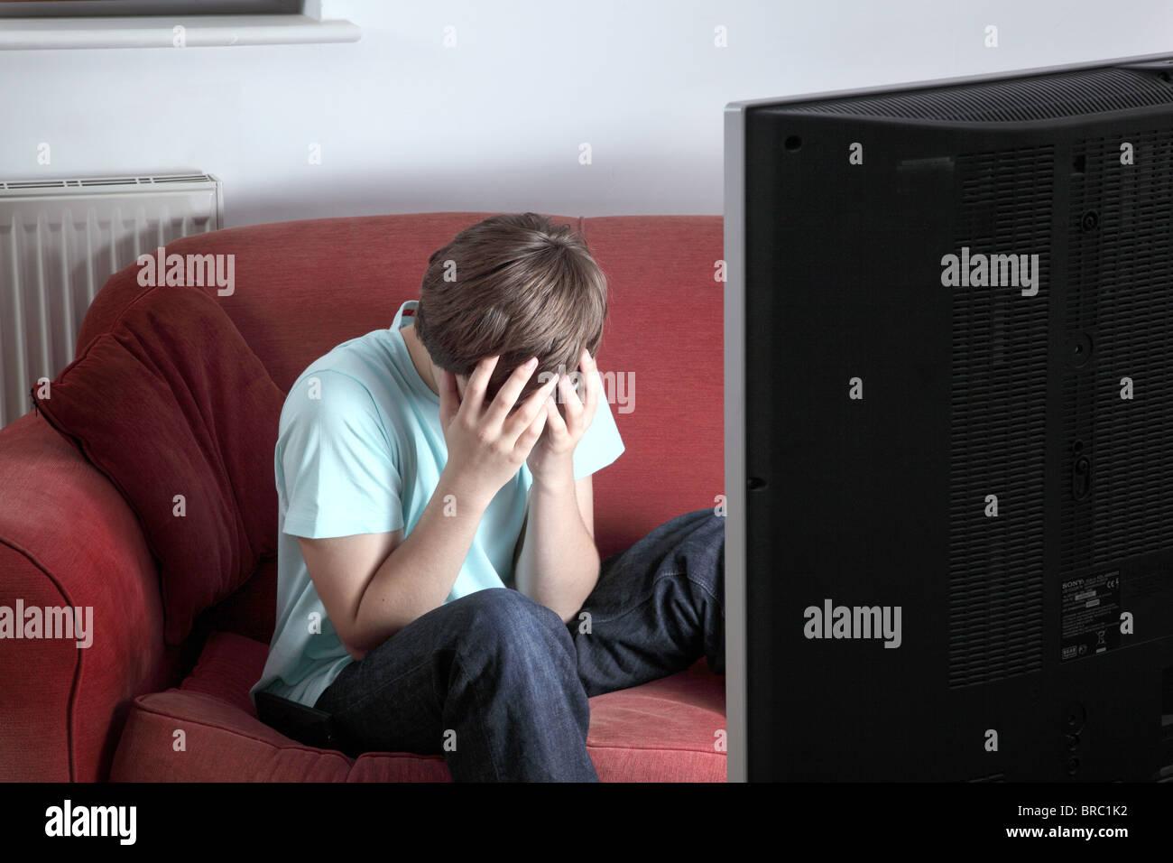 Macho joven con la cabeza entre las manos viendo la televisión Imagen De Stock