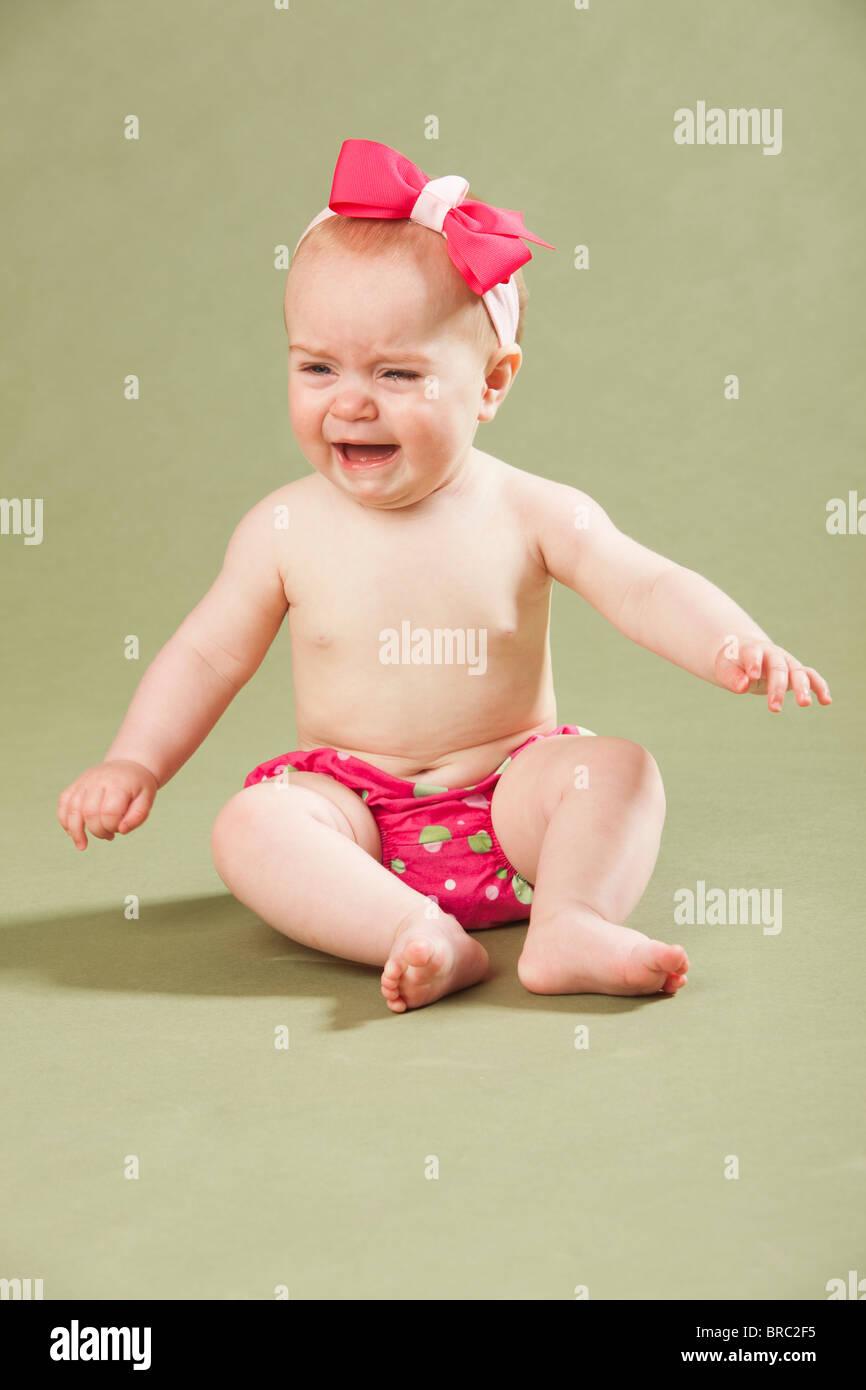 Baby Girl que llevaba un arco en su pelo y llorar Foto de stock
