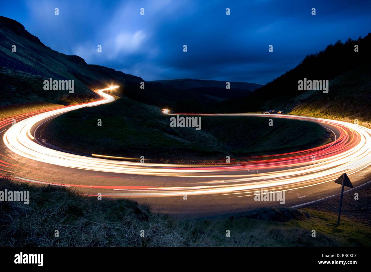 Los faros de los coches trailing alrededor de una curva cerrada en una mounatin pass en el sur de Gales. Imagen De Stock