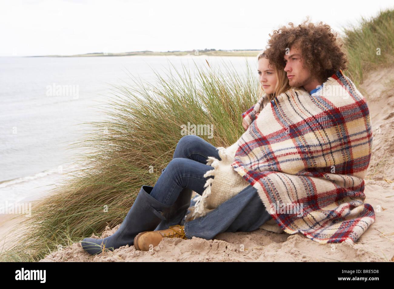 La pareja de adolescentes sentados en las dunas de arena envuelto en una manta Imagen De Stock