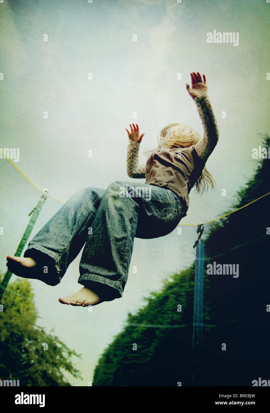Chica saltando sobre una cama elástica Imagen De Stock