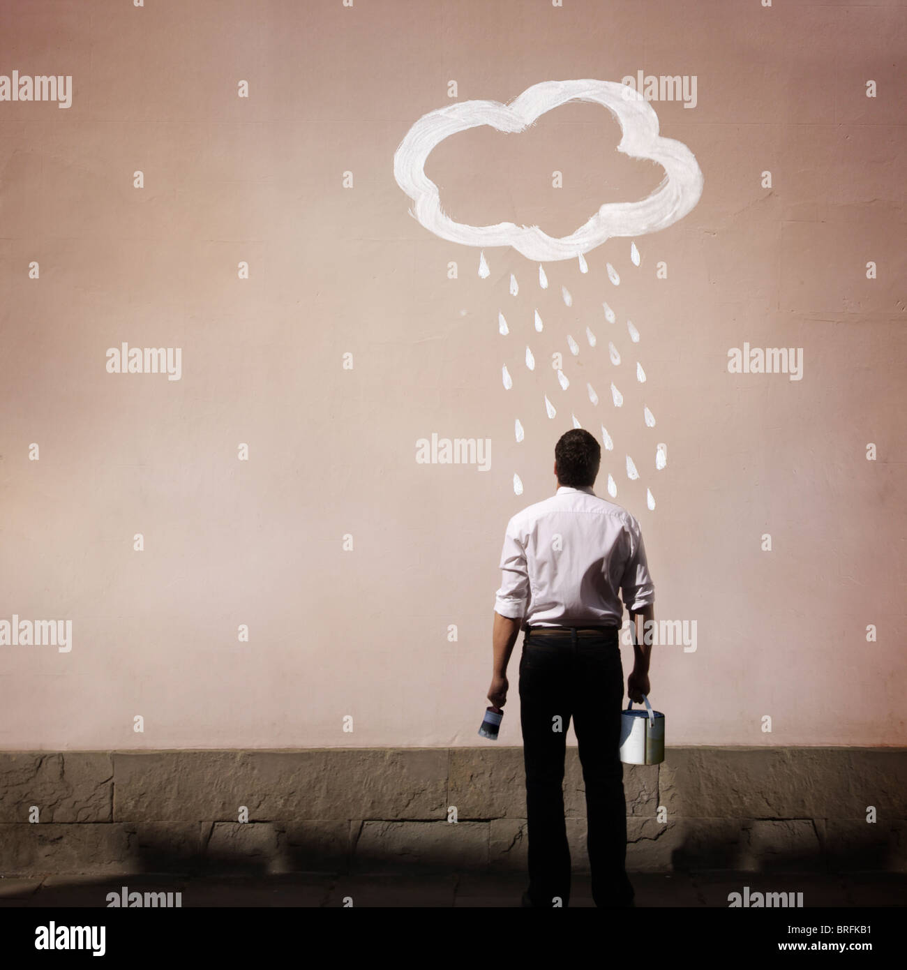 Hombre con nube de lluvia pintada en una pared. Imagen De Stock