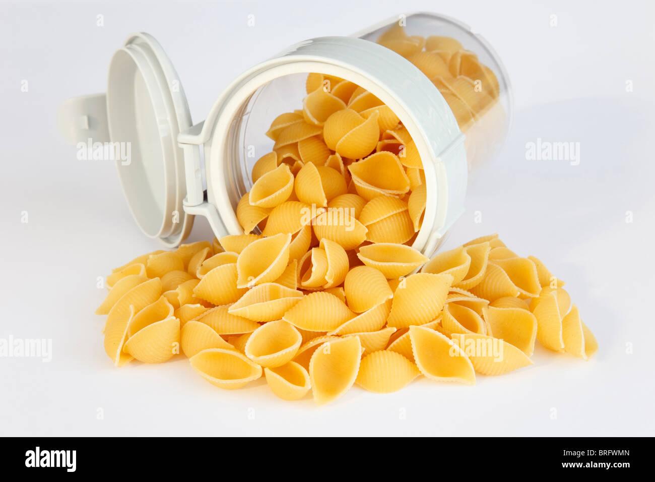 Montón de conchas de pasta Conchiglie crudos derramándose de un contenedor de comida de plástico Imagen De Stock