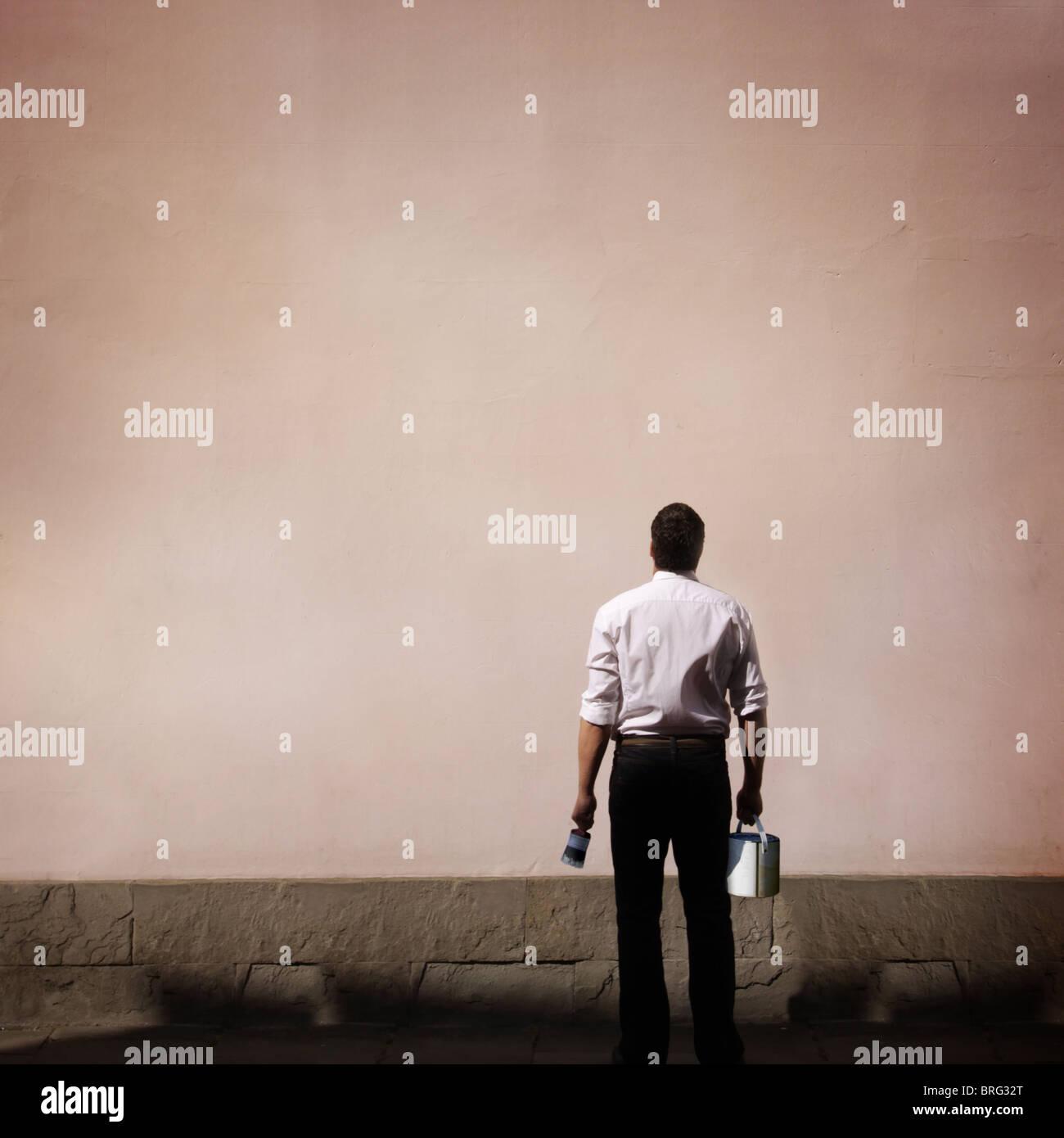 Hombre con pintura mirando una pared en blanco Imagen De Stock