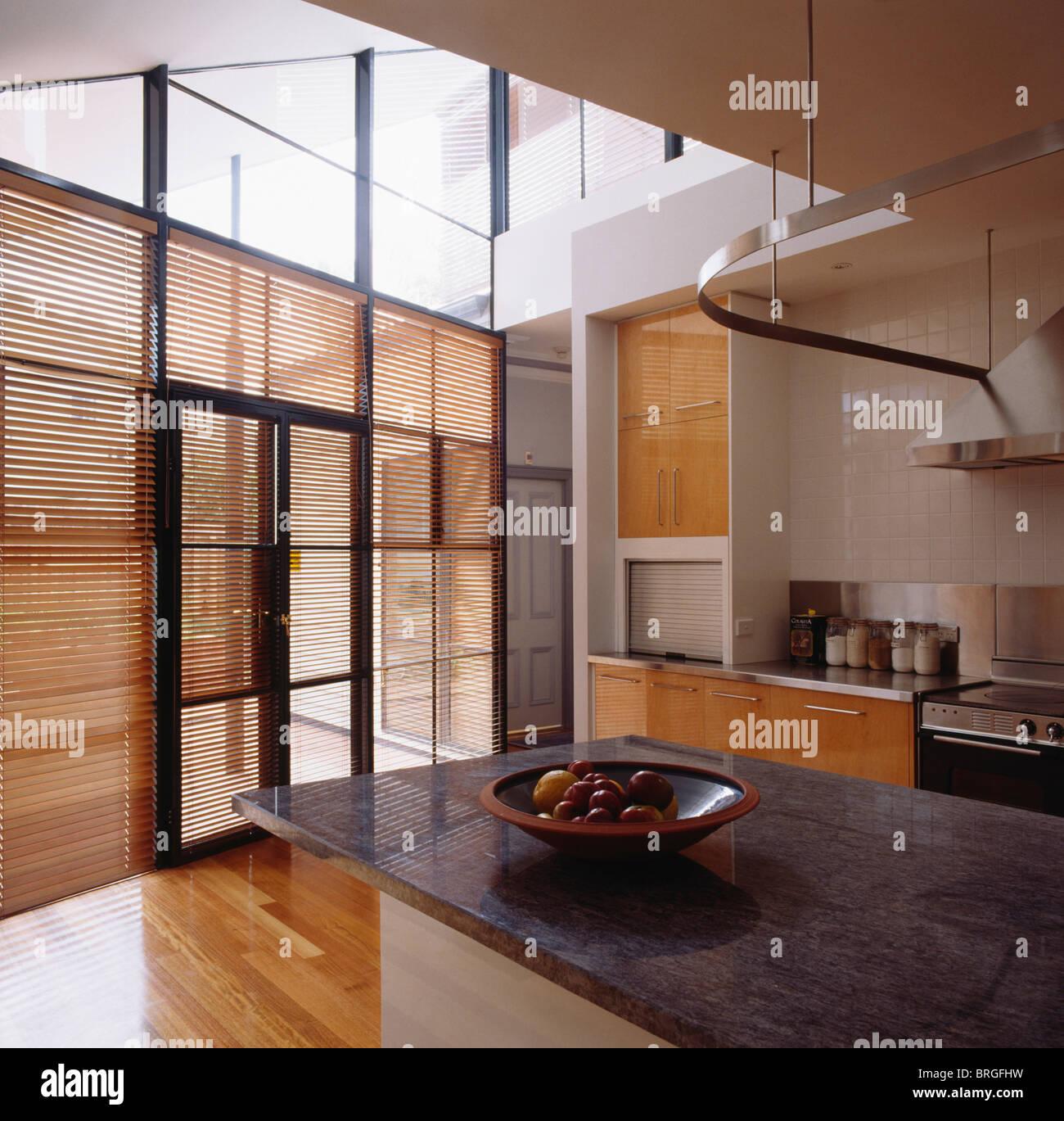 Persianas de madera en puertas de cristal en el gran ventanal de doble altura cocina moderna - Altura encimera cocina ...