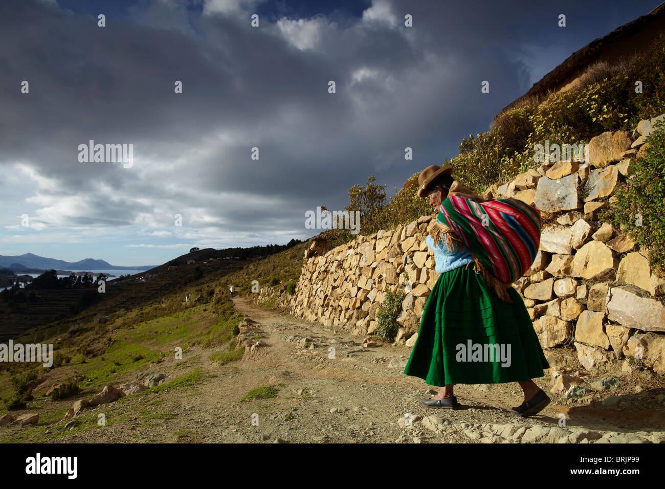 Una mujer con carga sobre su espalda, Isla del Sol, Lago Titicaca, Bolivia Foto de stock