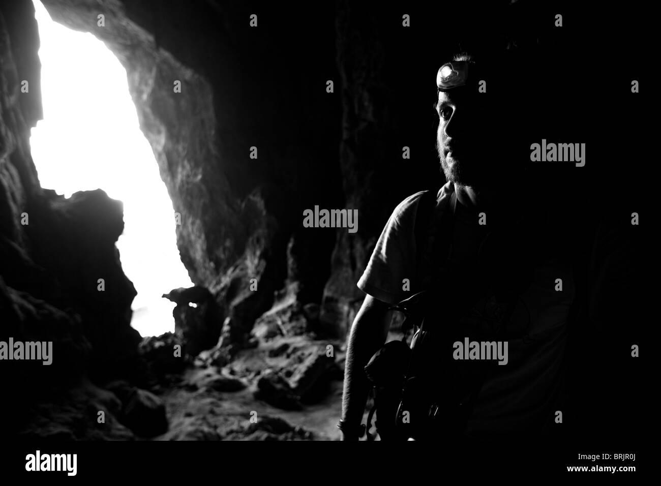 Macho barbudo explora una cueva de piedra caliza con su faro. Foto de stock