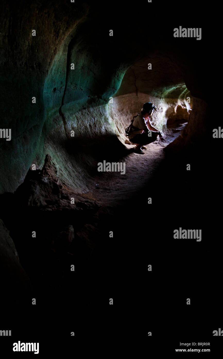 Caver masculino se sienta bajo en un túnel, mirando hacia la salida. Imagen De Stock