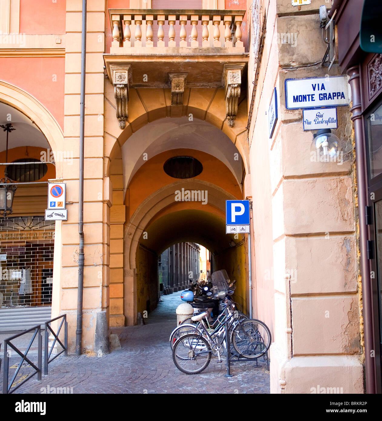 Via Monte Grappa con bicicletas aparcadas- una típica calle arqueada en Bolonia, Emilia-Romaña, Italia Foto de stock
