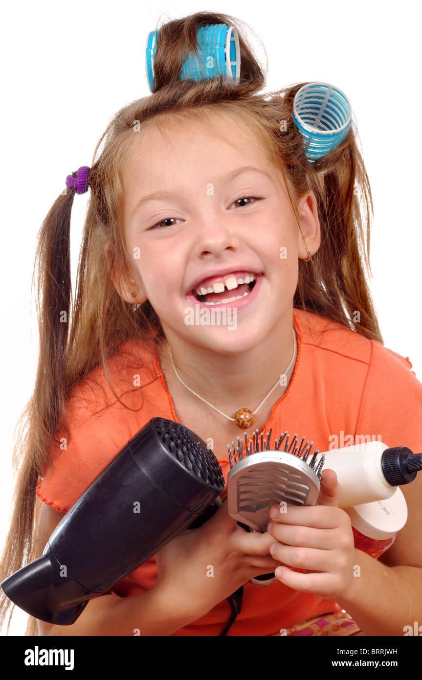 Chica con un peine en rizadores de pelo sobre un fondo blanco. Imagen De Stock