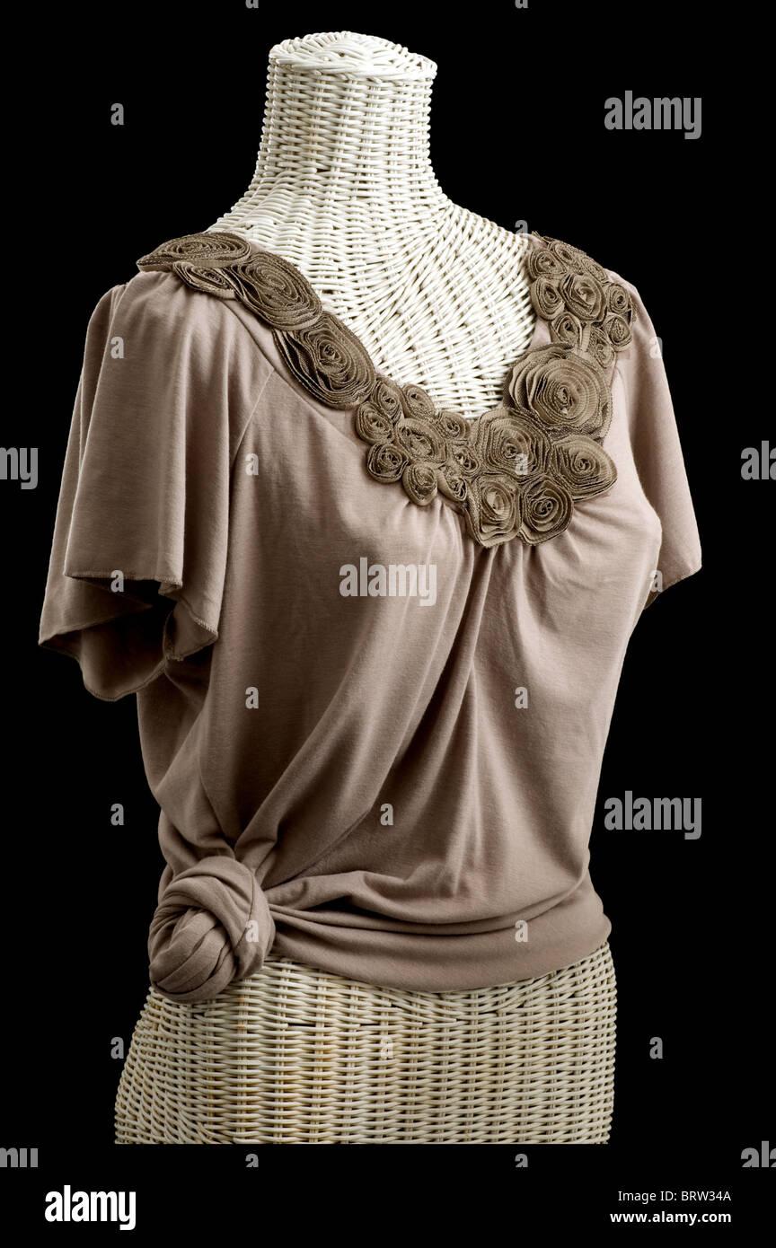 Flores de tejido del cuello de Blusa manga corta tejido de color beige. Blusa es atada y está sobre un maniquí Imagen De Stock
